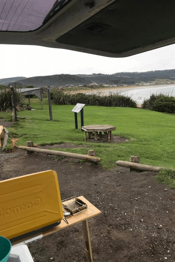 camping is one of the best things to do in the catlins and this photo is of me having lunch looking over curio bay