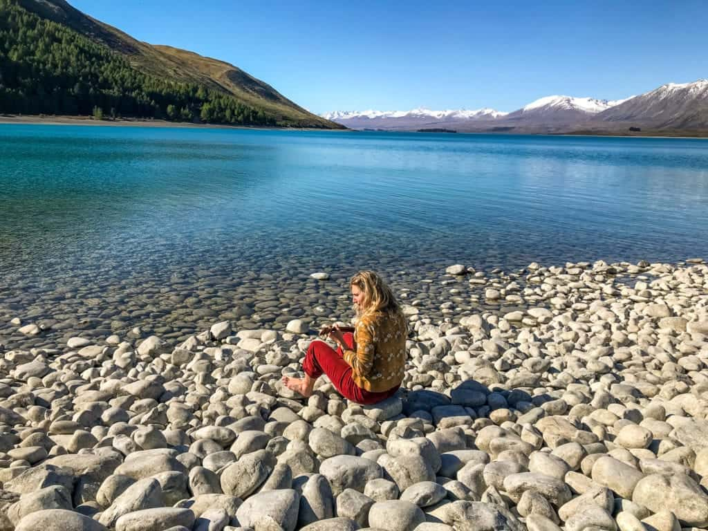 this is a photo of me playing ukelele in front of lake tekapo a typical destination on a south island road trip